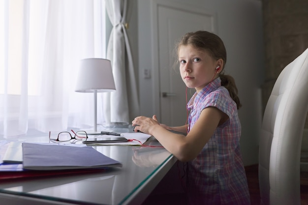 Dziecko dziewczynka 9, 10 lat siedzi w domu przy biurku przy oknie z zeszytami szkolnymi i tabletem cyfrowym, słuchawki w uszach, lekcje audio, technologia w edukacji