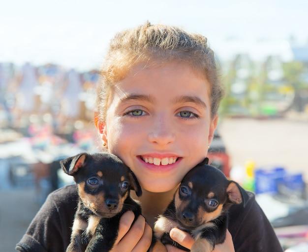 Dziecko dziewczynka bawi się z psami szczenię uśmiechając się