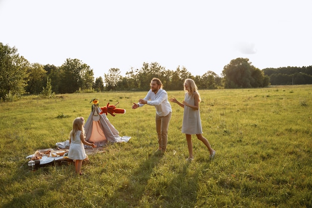 Dziecko dziewczynka bawi się z rodzicami letni piknik