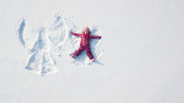 Dziecko dziewczynka bawić się anioła śniegu w śniegu i robić. płaski widok z góry