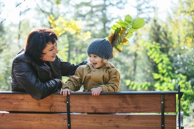 Dziecko dziewczynka ciepłą kurtkę i czapkę c babcia w jesiennym parku