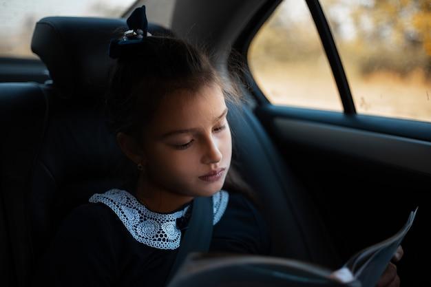 Dziecko dziewczynka czyta książkę wewnątrz samochodu w czasie ruchu.