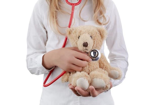 Dziecko dziewczynka gra lekarza z pluszową zabawką jako żłobek