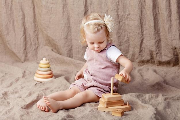 Dziecko dziewczynka gra z piramidy drewniane zabawki. mała śliczna dziewczyna z naturalnymi zabawkami.