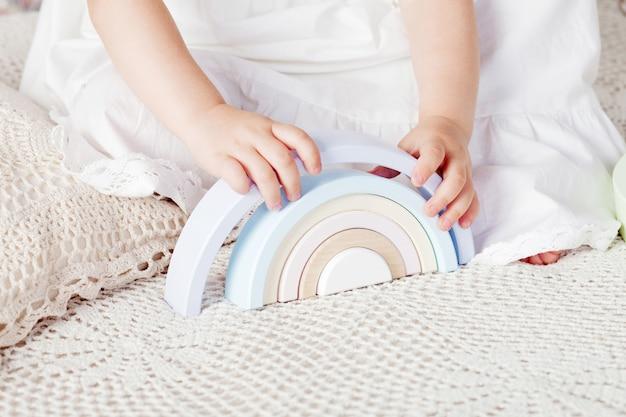 Dziecko dziewczynka gra z piramidy drewniane zabawki. ścieśniać