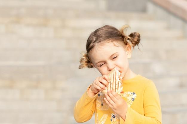 Dziecko dziewczynka gryzie kanapkę na ulicy. dziecko je zwykłą kromkę chleba na zewnątrz i cieszy się posiłkiem