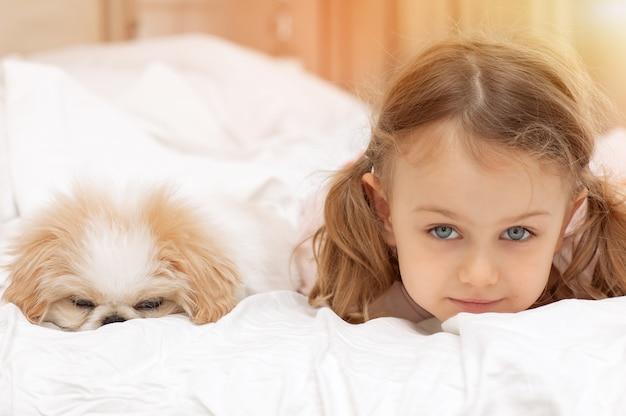 Dziecko dziewczynka i szczeniak bawią się i śpią na łóżku dom zwierzaka opieka nad zwierzętami