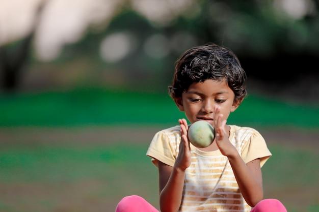Dziecko dziewczynka indyjski, grając z piłką