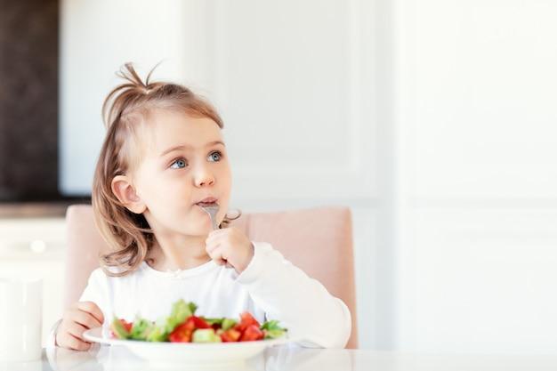 Dziecko dziewczynka jedzenie świeżych surowych warzyw sałatka witaminowa w tle białej kuchni i starannie patrzy na pustą przestrzeń kopii. zdrowe odżywianie żywności dla dzieci. miejsce na tekst reklamowy.