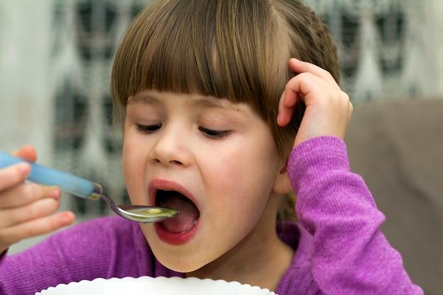Dziecko dziewczynka jedzenie zupy z płyty z łyżką
