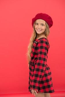 Dziecko dziewczynka ładny z długimi włosami pozowanie w czerwonym tle kapelusz. jak nosić francuski beret. inspiracja stylem beretu. jak nosić beret jak dziewczyna mody. modny dodatek do beretu dla kobiet.