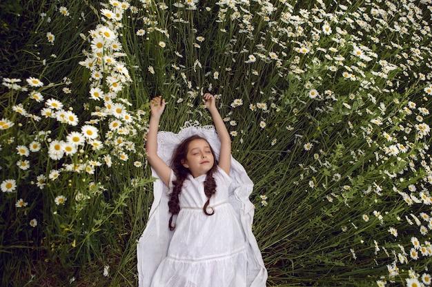 Dziecko dziewczynka leży na polu rumianku w białej sukni latem