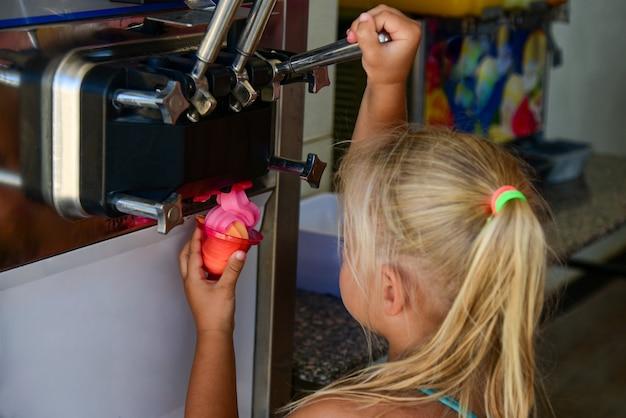 Dziecko dziewczynka odbiera lody w filiżance z automatu