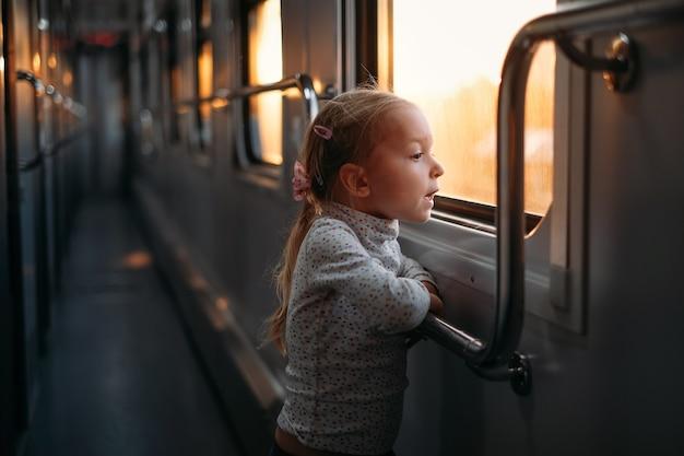 Dziecko dziewczynka patrząc przez okno pociągu na zachód słońca