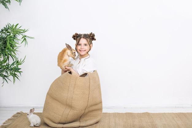 Dziecko dziewczynka piękna urocza wesoła i szczęśliwa w wiklinowej torbie z małymi zwierzętami królikami