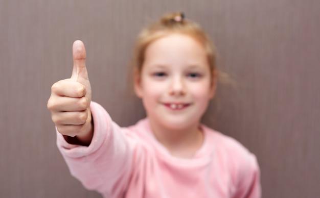 Dziecko dziewczynka pokazuje kciuk klasy