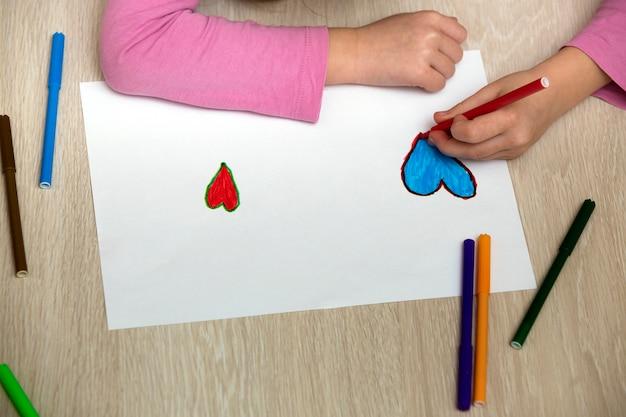 Dziecko dziewczynka ręce rysunek z kredkami kolorowe kredki serca na białym papierze. edukacja artystyczna, koncepcja kreatywności.