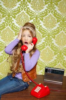 Dziecko dziewczynka retro rozmawiający wścibski w czerwony telefon