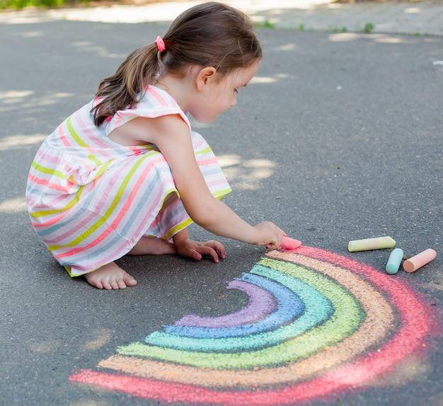 Dziecko dziewczynka rysuje tęczę z kolorową kredą na asfalcie.