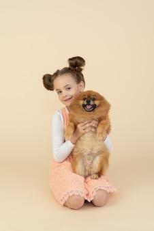 Dziecko dziewczynka siedzi i trzyma psa szpic