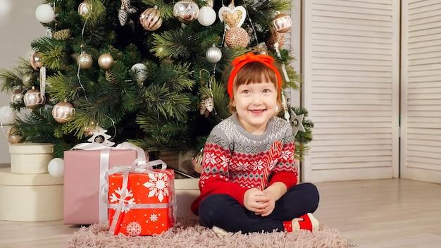 Dziecko dziewczynka siedzi pod choinką śmiejąc się podczas sesji zdjęciowej