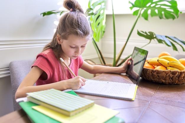 Dziecko dziewczynka studiuje w domu za pomocą cyfrowego tabletu. kształcenie na odległość, lekcja online, wideokonferencja, lekcje szkolne w formie elektronicznej. nowoczesna szkoła, technologia, edukacja, koncepcja dzieci.
