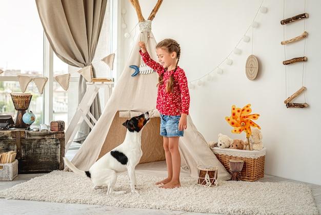 Dziecko dziewczynka szkolenia psa foksterier w lekkim pokoju dziecięcym
