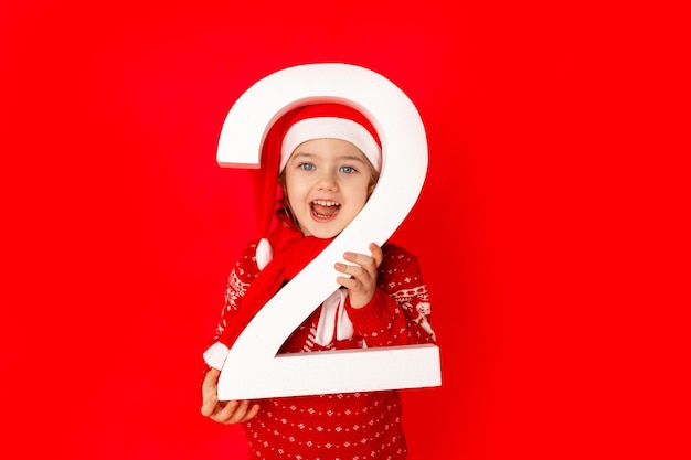 Dziecko dziewczynka trzyma numer dwa w czapce świętego mikołaja na czerwonym tle, miejsce na tekst