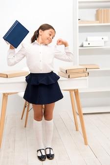 Dziecko dziewczynka trzymać książkę podczas rozciągania białego wnętrza. dziecięcy mundurek szkolny, dzięki któremu ćwiczenia rozciągające zwiększają produktywność. ćwiczenia podtrzymujące żywotność. rola przerw aktywnych w procesie edukacyjnym.