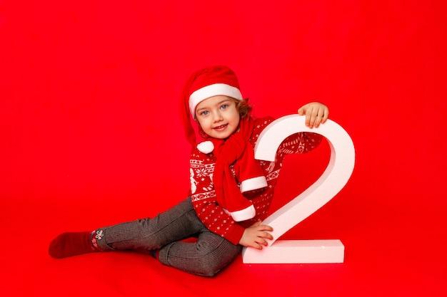 Dziecko dziewczynka trzymająca numer dwa w zimowych ubraniach na czerwonym tle, miejsce na tekst