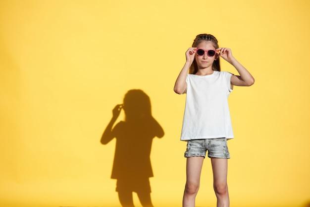 Dziecko dziewczynka ubrana w białą koszulkę z na żółtym tle