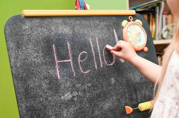 Dziecko dziewczynka uczy się pisać na desce kreślarskiej w domu.