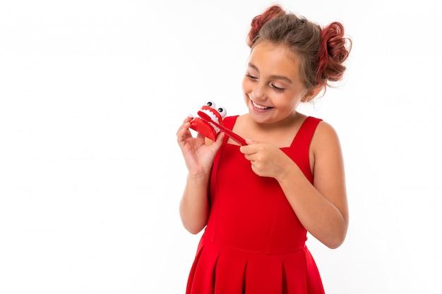 Dziecko dziewczynka uczy szczotkowania zębów na białym tle, trzyma w rękach szczoteczkę do zębów i układ zębów szczęki z zębami