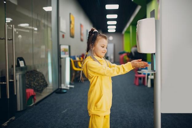 Dziecko dziewczynka używająca automatycznego dozownika żelu alkoholowego spryskującego ręce maszyna do dezynfekcji rąk antyseptyczny środek dezynfekujący nowe normalne życie po pandemii koronawirusa