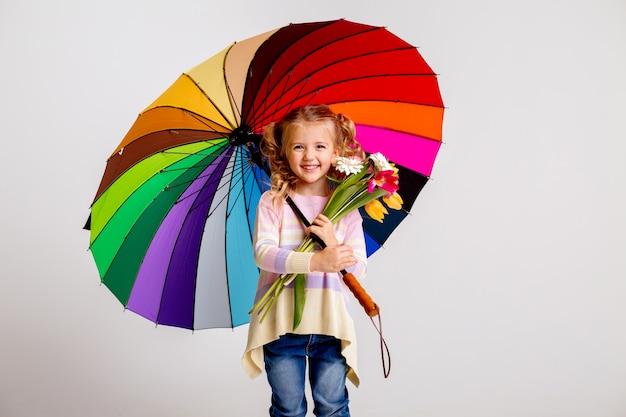 Dziecko dziewczynka w gumowe buty gospodarstwa wielobarwny parasol