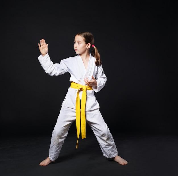 Dziecko dziewczynka w karate garnitur z postawy żółty pasek pokazuje