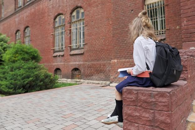 Dziecko dziewczynka w mundurze z plecakiem siedzi w szkolnym dziedzińcu czytanie notebooka, miejsce. powrót do szkoły, początek zajęć, edukacja, wiedza, lekcje, koncepcja dzieci