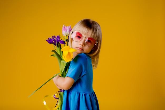 Dziecko dziewczynka w okulary w niebieskie ubrania, uśmiechając się i trzyma bukiet kwiatów na żółtym tle izolowania