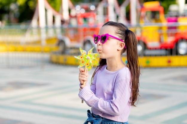 Dziecko dziewczynka w parku rozrywki latem wieje na zabawkowej przędzarce w pobliżu karuzeli w okularach przeciwsłonecznych, koncepcja wakacji letnich i wakacji szkolnych