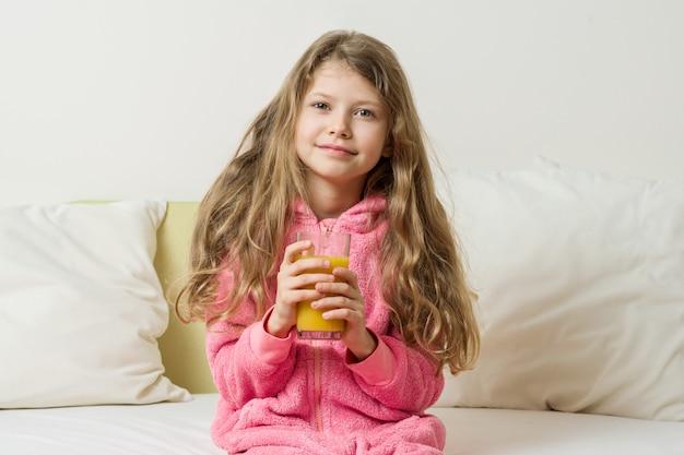 Dziecko dziewczynka w piżamie ze szklanką świeżego soku pomarańczowego