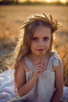 Dziecko dziewczynka w sukience i wieniec na głowie siedzieć na skoszonym polu pszenicy o zachodzie słońca latem