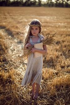 Dziecko dziewczynka w sukience i wieniec na głowie stoi na skoszonym polu pszenicy o zachodzie słońca latem