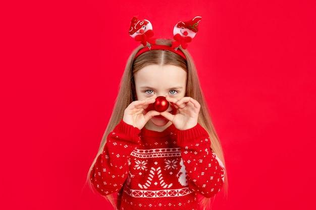 Dziecko dziewczynka w swetrze z piłką na nosie na czerwonym monochromatycznym na białym tle raduje się i uśmiecha, koncepcja nowego roku i bożego narodzenia, miejsca na tekst