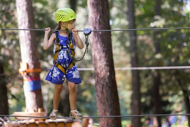 Dziecko dziewczynka w uprząż bezpieczeństwa i kask na sposób liny