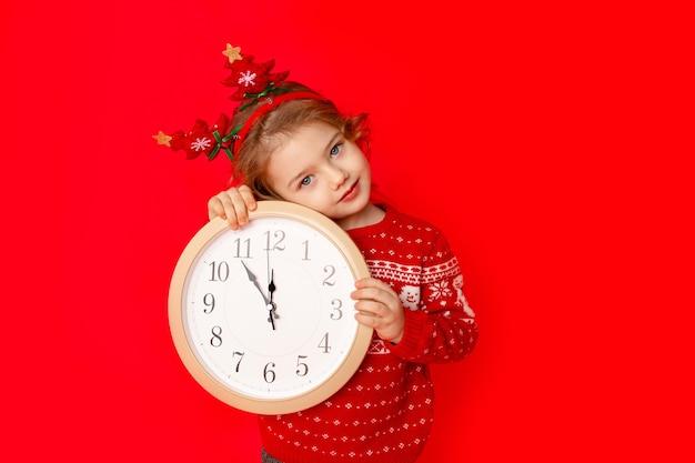 Dziecko dziewczynka w zimowe ubrania trzyma zegarek na czerwonym tle. noworoczna koncepcja, miejsce na tekst
