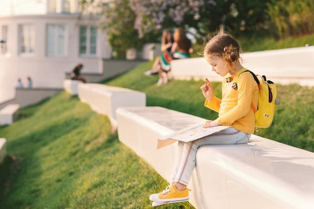 Dziecko dziewczynka w żółtych ubraniach z plecakiem, czytanie książki na leżaku w słonecznym parku na świeżym powietrzu latem. powrót do szkoły.