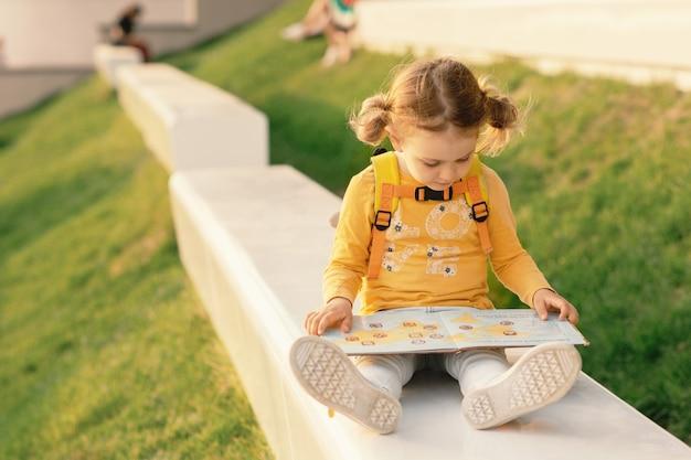 Dziecko dziewczynka w żółtych ubraniach z plecakiem z książką do czytania na leżaku w słonecznym parku w lecie