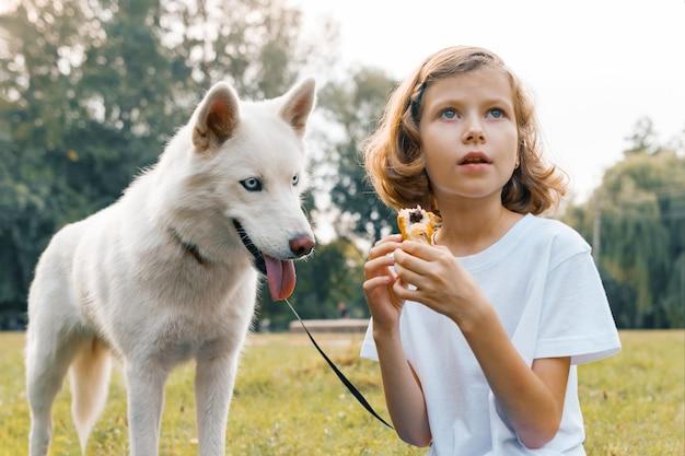 Dziecko dziewczynka z białym psem husky