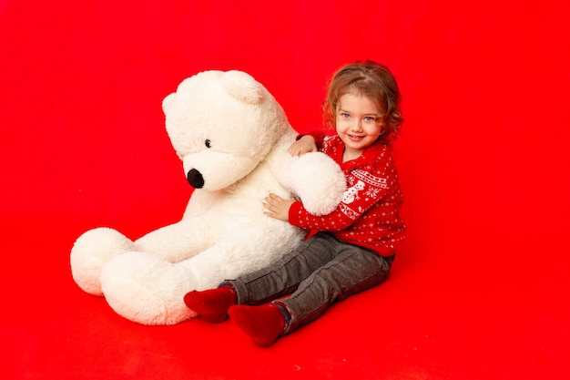 Dziecko dziewczynka z dużym misiem w zimowych ubraniach na czerwonym tle, miejsce na tekst