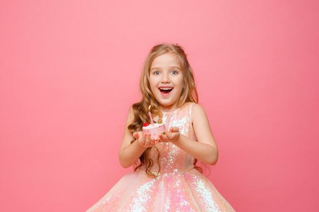 Dziecko dziewczynka z świątecznym tortem zdmuchuje świecę na kolorowym